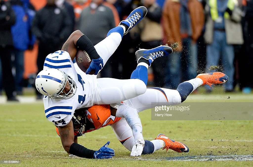 Hakeem Nicks #14 of the Indianapolis Colts is tackled by Bradley Roby #29 of the Denver Broncos after a catch during a 2015 AFC Divisional Playoff game at Sports Authority Field at Mile High on January 11, 2015 in Denver, Colorado.