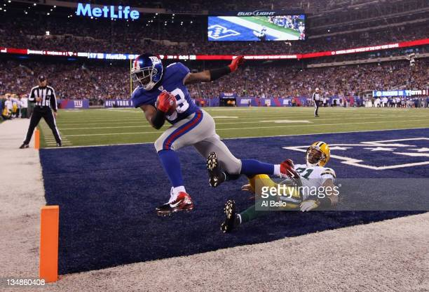Hakeem Nicks of the New York Giants catches a 4yard touchdown reception in the third quarter against Charles Woodson of the Green Bay Packers at...