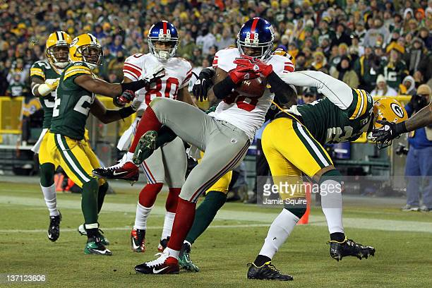 Hakeem Nicks of the New York Giants makes a 37 yard touchdown catch with time running out in the second quarter against Charles Woodson of the Green...
