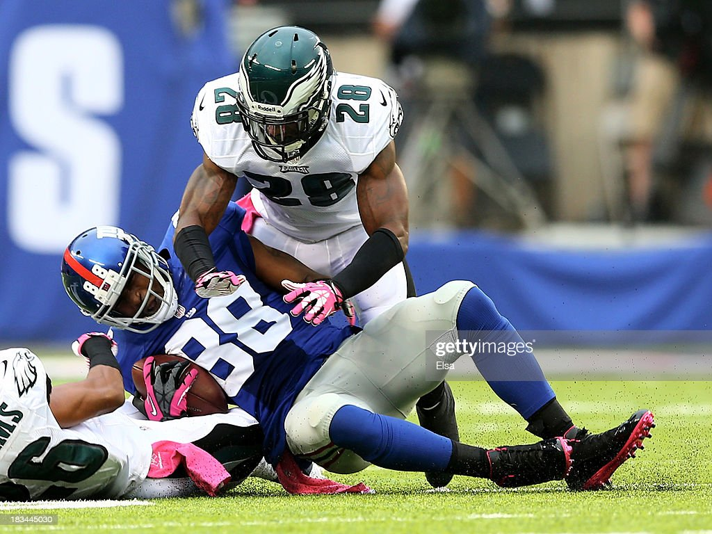 Hakeem Nicks #88 of the New York Giants makes the catch in the first quarter as Cary Williams #26 and Earl Wolff #28 of the Philadelphia Eagles defend at MetLife Stadium on October 6, 2013 in East Rutherford, New Jersey.