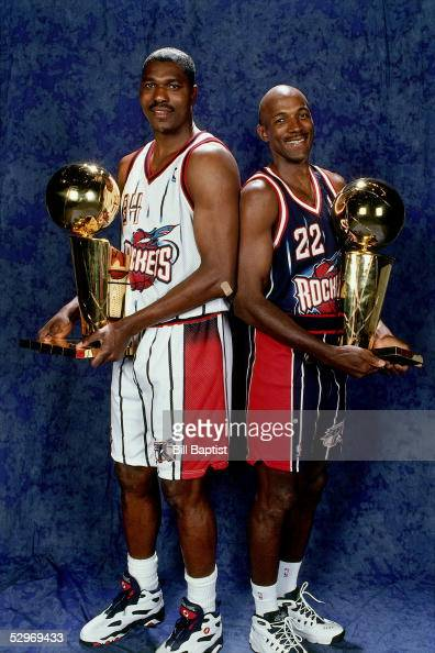 Hakeem Olajuwon and Clyde Drexler of the Houston Rockets pose for a portrait with two NBA Champiionship Trophies in Houston Texas NOTE TO USER User...