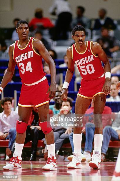 Hakeem Olajuwon and Ralph Sampson of the Houston Rockets eye the play during an NBA game against the Los Angeles Clippers circa 1986 in Los Angeles...