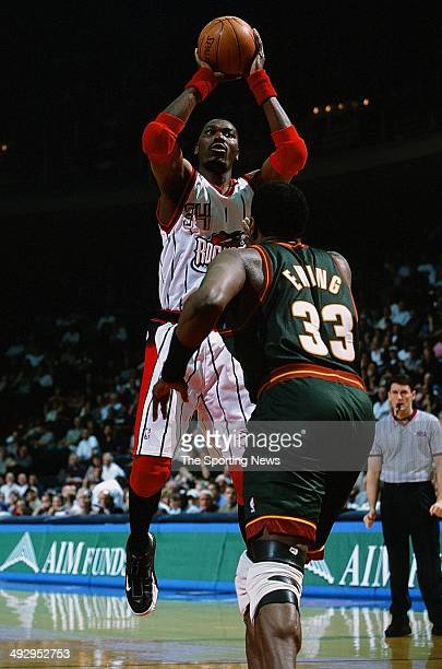 Hakeem Olajuwon of the Houston Rockets goes up for a shot over Patrick Ewing of the Seattle SuperSonics during the game on April 5 2001 at the Compaq...