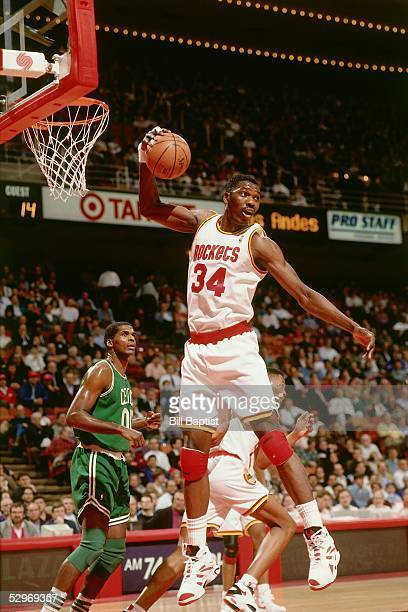 Hakeem Olajuwon of the Houston Rockets grabs a rebound against the Boston Celtics during an NBA game at the Compaq Center circa 1994 in Houston Texas...