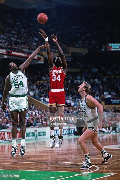 Hakeem Olajuwon of the Houston Rockets shoots a jump shot against Ed Pinckney and Larry Bird of the Boston Celtics during a game played in 1990 at...
