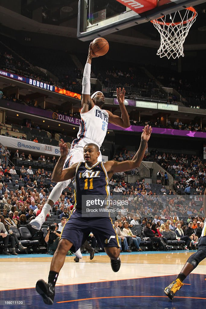 Hakim Warrick #21 of the Charlotte Bobcats dunks over the head of Earl Watson #11 of the Utah Jazz at the Time Warner Cable Arena on January 9, 2013 in Charlotte, North Carolina.