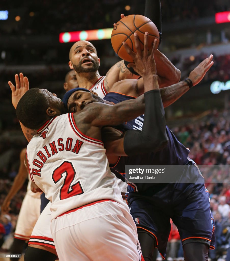 Hakim Warrick #21 of the Charlotte Bobcats grabs a rebound between Nate Robinson #2 and Carlos Boozer #5 of the Chicago Bulls at the United Center on December 31, 2012 in Chicago, Illinois. The Bobcats defeated the Bulls 91-81.