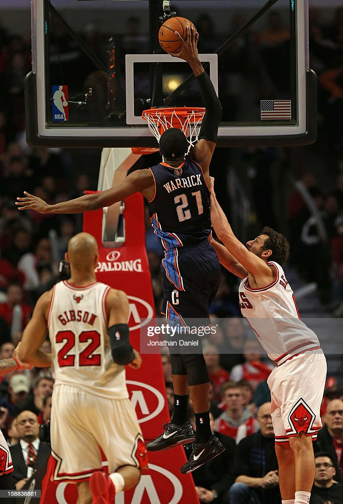 Hakim Warrick of the Charlotte Bobcats leaps for a dunk over Taj Gibson and Marco Belinelli of the Chicago Bulls at the United Center on December 31...