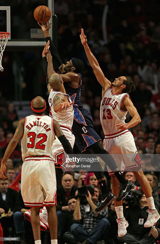 Hakim Warrick #21 of the Charlotte Bobcats puts up a shot over (L-R) Richard Hamilton #32, Carlos Boozer #5 and Joakim Noah #13 of the Chicago Bulls at the United Center on December 31, 2012 in Chicago, Illinois. The Bobcats defeated the Bulls 91-81.