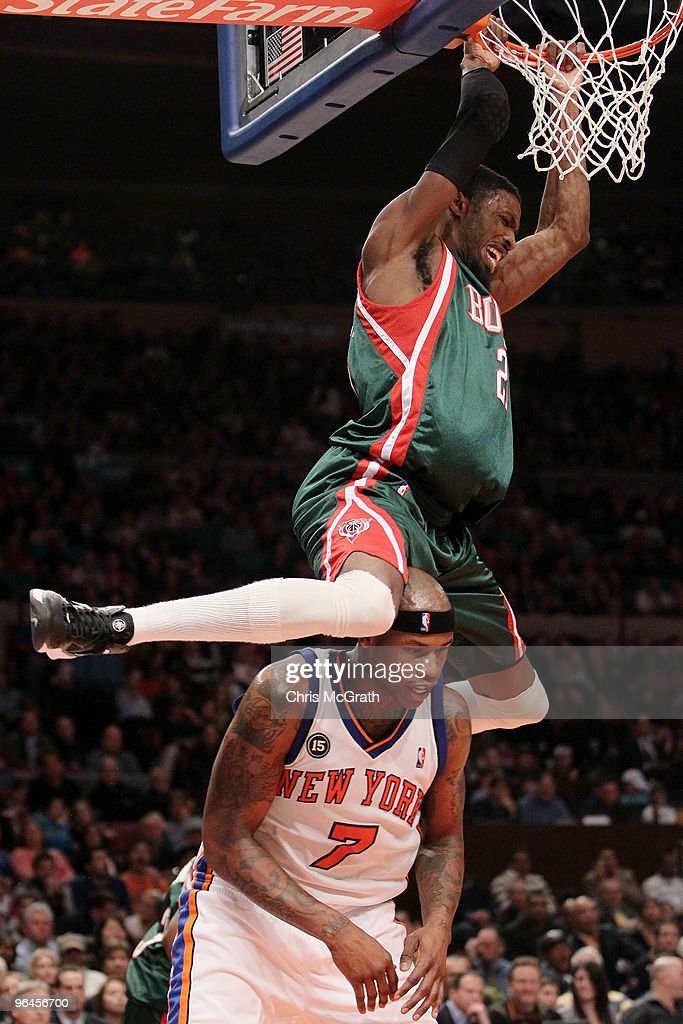 Hakim Warrick of the Milwaukee Bucks swings on the ring after dunking on Al Harrington of the New York Knicks at Madison Square Garden February 5...