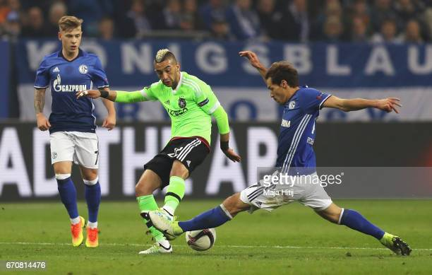 Hakim Ziyech of Ajax is challenged by Benjamin Stambouli of FC Schalke 04 during the UEFA Europa League quarter final second leg match between FC...