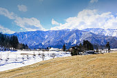 Hakuba mountain range  and  Hakuba village houses  in the winter with snow on the mountain and blue sky and clouds background in Hakuba  Nagano Japan.