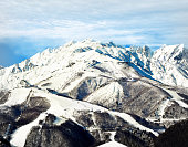 Hakuba mountain range in the afternoon early winter. The gondola and chair lifts visible are located on the top third of the mountain. The mountains massive size is noticeable against the tiny chair l