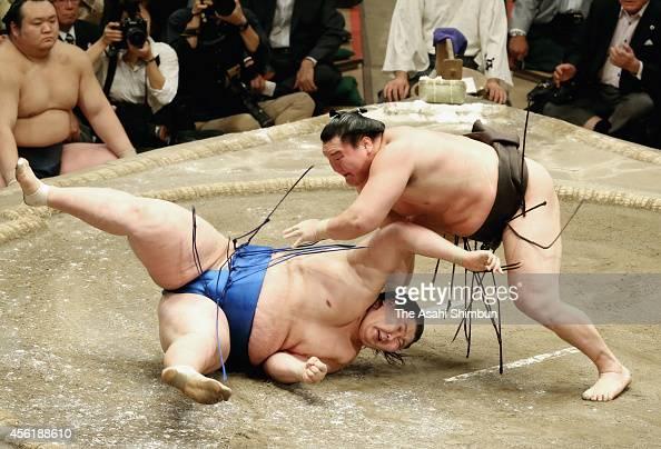Hakuho throws Ichinojo to win on the day fourteen of Grand Sumo Autumn Tournament at Ryogoku Kokugikan on September 27 2014 in Tokyo Japan