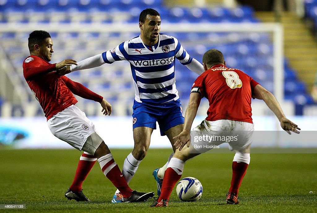 Hal Robson-Kanu of Reading holds off pressure from Reuben Noble-Lazarus (L) and Stephen Dawson (R) of Barnsley during the Sky Bet Championship match between Reading and Barnsley at Madejski Stadium on March 25, 2014 in Reading, England,