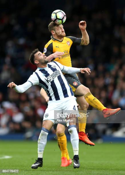 Hal RobsonKanu of West Bromwich Albion and Shkodran Mustafi of Arsenal battle to win a header during the Premier League match between West Bromwich...