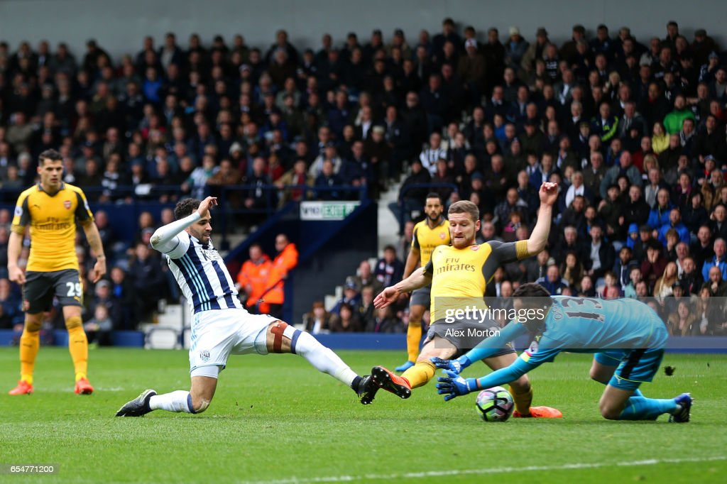 Hal Robson-Kanu of West Bromwich Albion (L) scores his sides second goal past David Ospina of Arsenal (R) during the Premier League match between West Bromwich Albion and Arsenal at The Hawthorns on March 18, 2017 in West Bromwich, England.