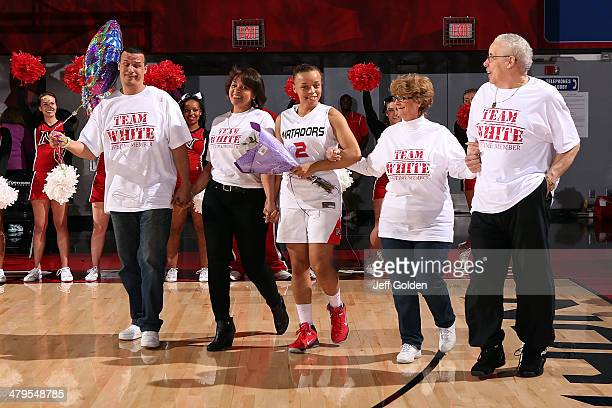 Haley White of the Cal State Northridge Matadors walks with her family to center court to be honored on senior night after the game against the UC...