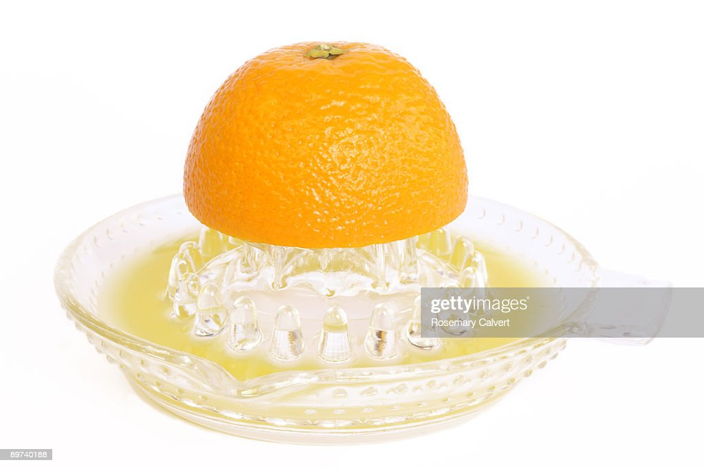 Half an orange being juiced. : Stock Photo