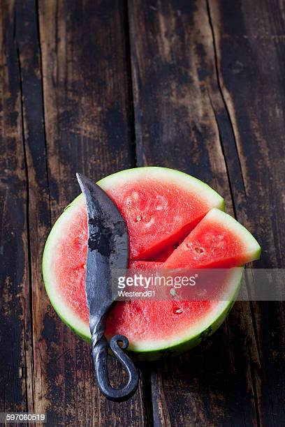 Half and piece of mini watermelon and knife on dark wood