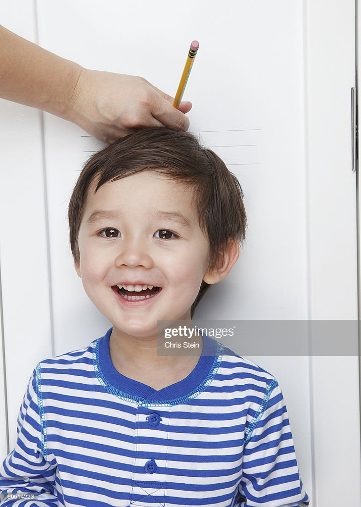 Half Asian boy getting his height measured