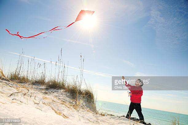 Half Asian Young Boy FLying a Red Kite on Beach