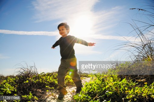 Half Asian Young Boy Running on a Beach Path : Stock Photo