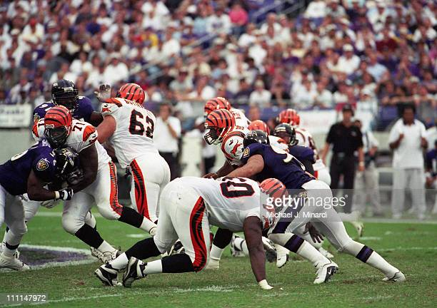 Half Back Brandon Bennett of the Cincinnati Bengals breaks through the Baltimore Ravens front line for some extra yardage with the help of his...