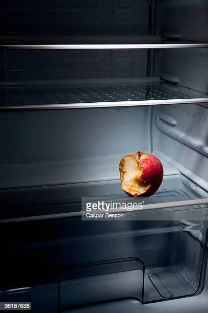 A half eaten apple in an empty refrigerator
