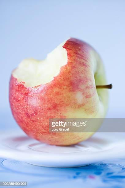 Half eaten apple on dish (focus on apple)