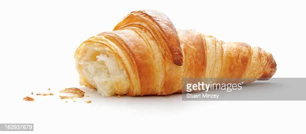 Half eaten croissant on white background
