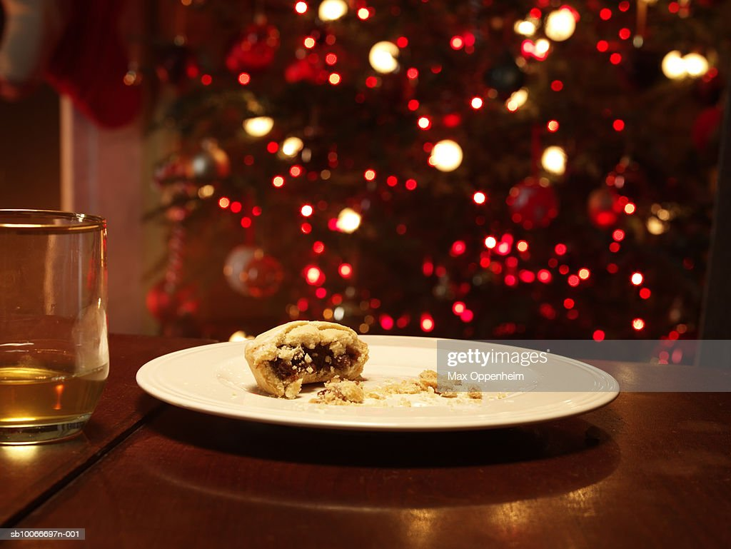 Half eaten mince pie on empty plate Christmas tree behind  Stock Photo & Half Eaten Mince Pie On Empty Plate Christmas Tree Behind Stock ...