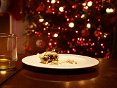 Half eaten mince pie on empty plate, Christmas tree behind