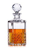 A half full crystal whisky decanter, with amber alcohol, shot on white, with a small reflection
