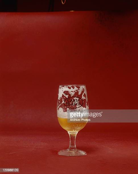 Half full glass of beer on red background