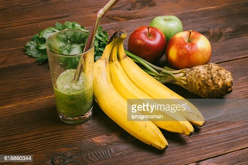 Half full glass of smoothie with straw, banana, celery root : Stock Photo