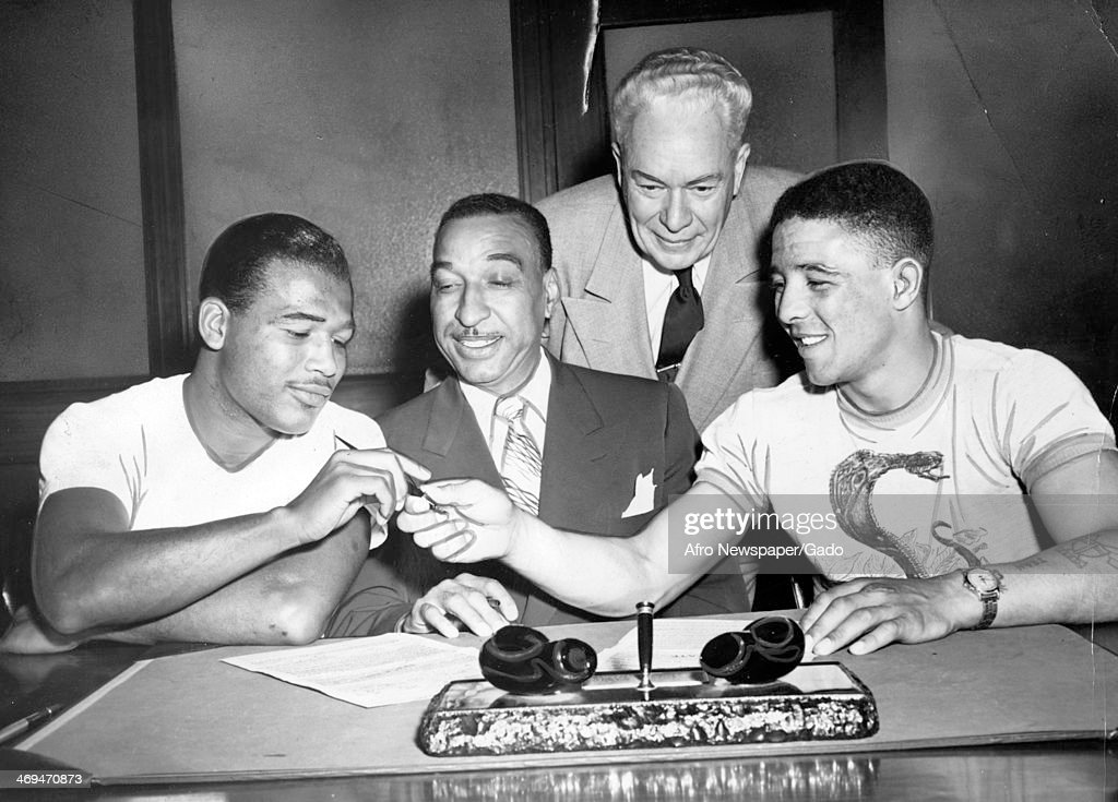 A half length portrait of boxing champion Sugar Ray Robinson and British boxer Randy Turpin signing the official title fight contract witnessed by...