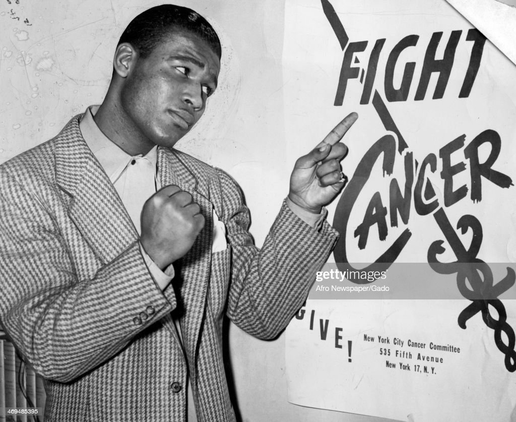 A half length portrait of boxing champion Sugar Ray Robinson pointing at a 'Fight Cancer' poster by the New York City Cancer Committee raising cancer...