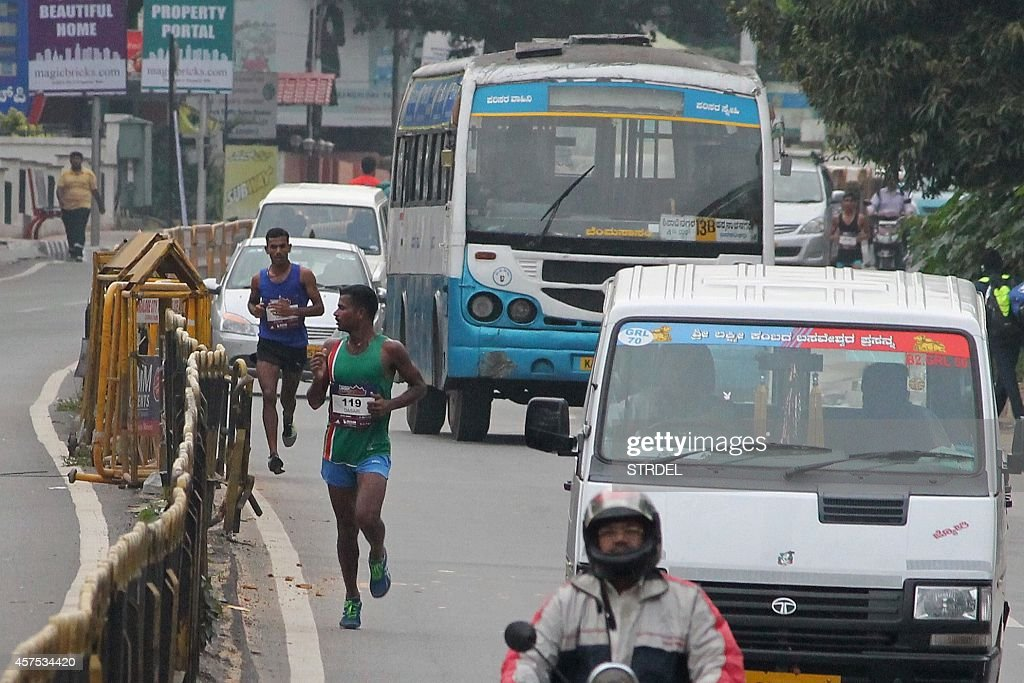 Half marathon participants run amid heavy traffic during the 'Bengaluru Marathon' in Bangalore on October 19 2014 A marathon ended in farce in India...