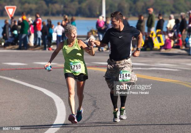 Half marathon runners Michaela Hood of Plymouth Massachusetts and Douglas Kerr of Raymond hold hands as they near the finish line during the Maine...
