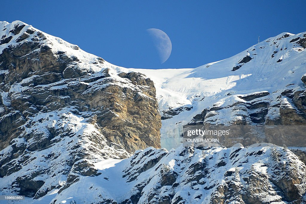 Half moon appears behind mountains during the men's World Cup Super Combined on January 18, 2012 in Wengen. France's Alexis Pinturault (C) won ahead of Croatia's Ivica Kostelic and Switzerland's Carlo Janka. AFP PHOTO / OLIVIER MORIN