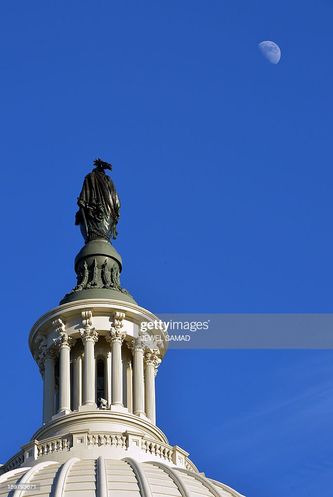 A half moon appears on the sky as seen near the Capitol dome while final preparations continue on January 20, 2013 for US President Barack Obama's second inauguration in Washington, DC. Obama was sworn in by Chief Justice John Roberts for a second term in office January 20, 2013 in a brief, intimate private ceremony at the White House. AFP PHOTO/Jewel Samad