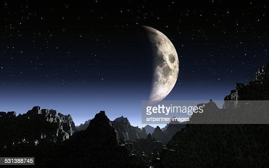 Half moon shinning over dark mountains at night