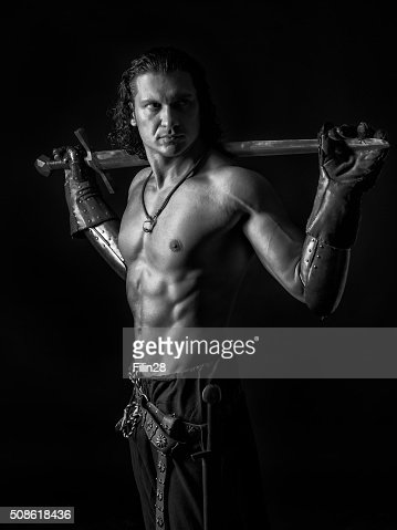 half naked man with a sword in medieval clothes : Stock Photo