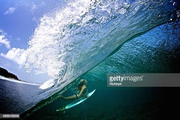 Half over half under girl duck diving a breaking wave
