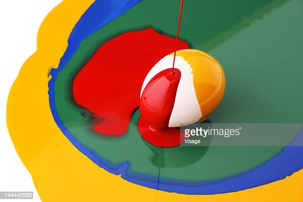 A half painted egg amidst colourful paints