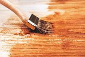 Varnishing a wooden shelf in brown using paintbrush