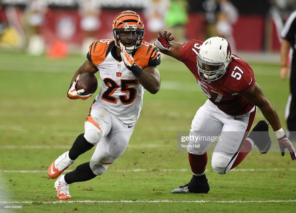 Halfback Giovani Bernard of the Cincinnati Bengals breaks up field past linebacker Alex Okafor of the Arizona Cardinals during a NFL preseason game...
