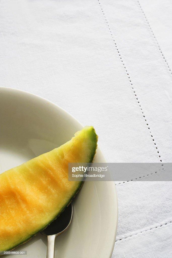 Half-eaten slice of melon on plate, close-up : Stock Photo