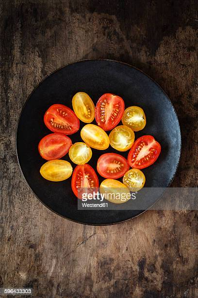 Halfed yellow and red cherry tomatoes on plate